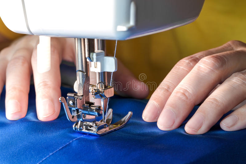 Sewing process, front view. Sewing process, women`s hands behind her work on sewing machine, closeup front view royalty free stock photo