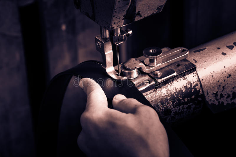 Sewing process of the leather belt. Man's hands behind sewing. Leather workshop. Black and white photography royalty free stock photo