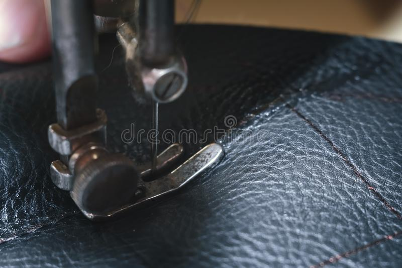 Sewing process of the leather belt. old Man`s hands behind sewing. Leather workshop. textile vintage sewing industrial royalty free stock images