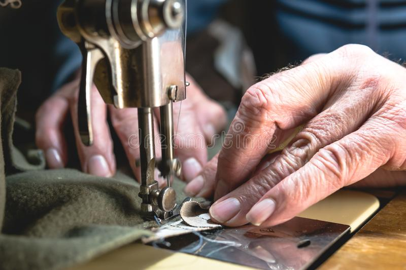 Sewing process of the leather belt. old Man`s hands behind sewing. Leather workshop. textile vintage sewing industrial royalty free stock image