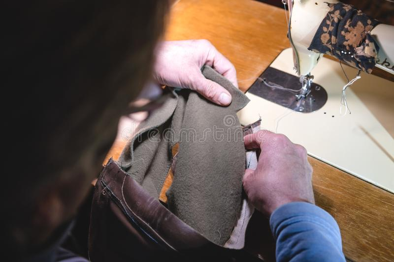 Sewing process of the leather belt. old Man`s hands behind sewing. Leather workshop. textile vintage sewing industrial royalty free stock photo