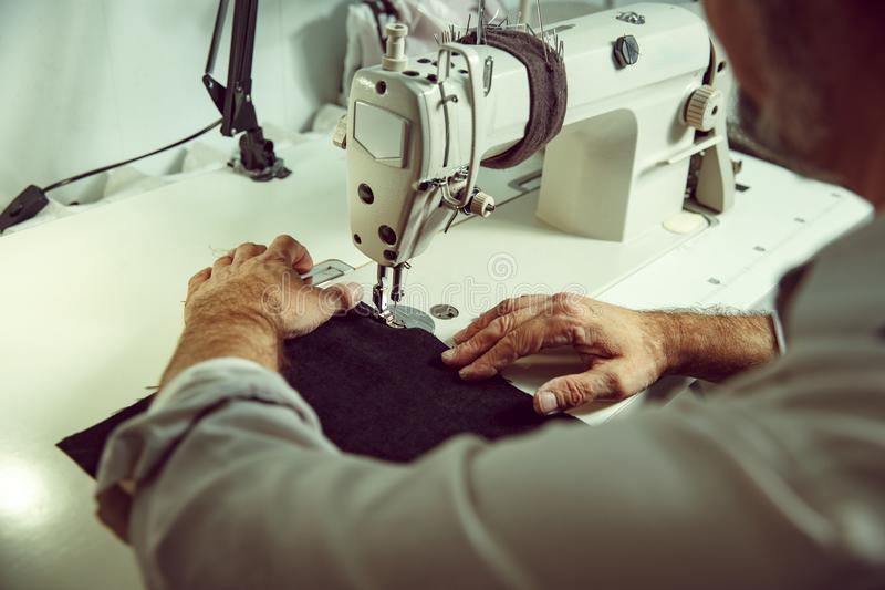 Sewing process of the leather belt. old Man`s hands behind sewing. royalty free stock images