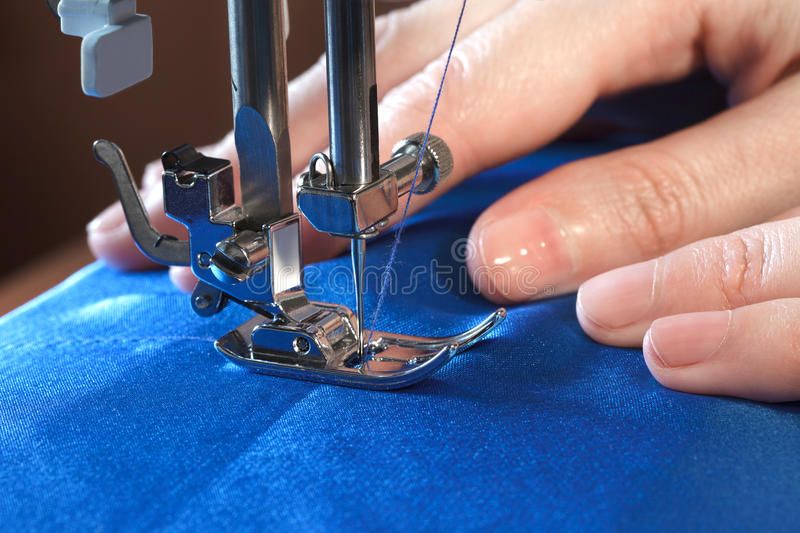 Sewing process, side view. Sewing process, women`s hands behind her work on sewing machine, closeup side view royalty free stock photo