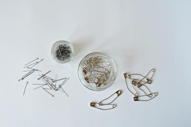 Sewing and quilting pins in glass jars. Over white stock photo