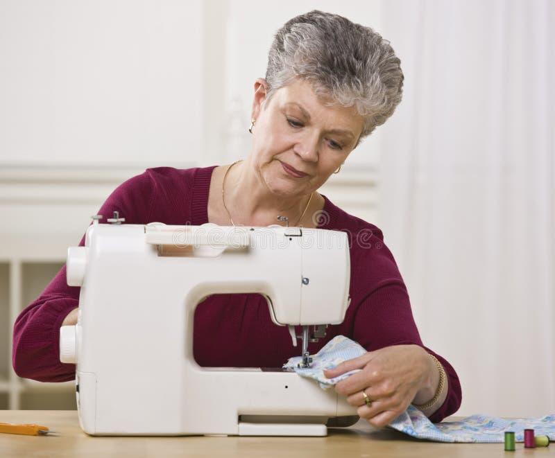 Sewing sênior da mulher imagens de stock