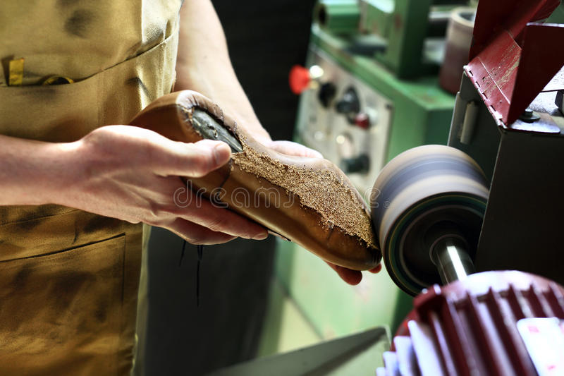 Sewing shoes. Shoemaker makes chisel holes in the skin grain stock photos