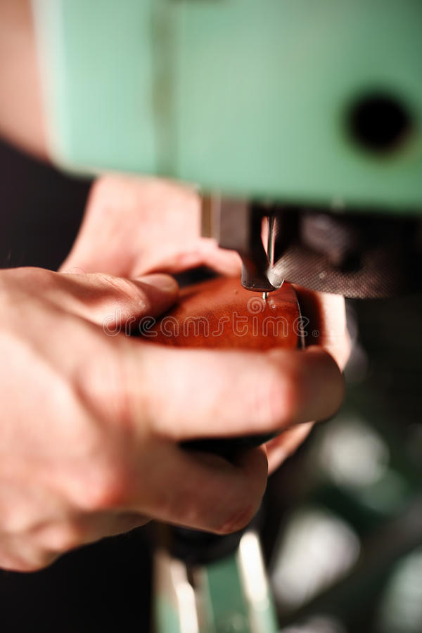 Sewing shoes. Shoemaker in the studio craftsmen hand-sews shoes stock photo