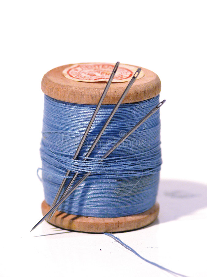 Sewing spool with a needle. A sewing needle. Color stock images