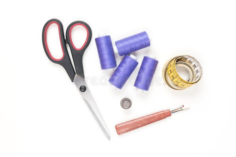 Sewing supplies and tools, medium purple threads, yellow tape with black numbers, big scissors, metal thimblele stock photography
