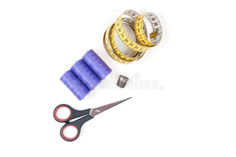 Sewing supplies and tools, purple sewing threads, yellow measuring tape with black numbers, small closed scissors and metal th royalty free stock photo