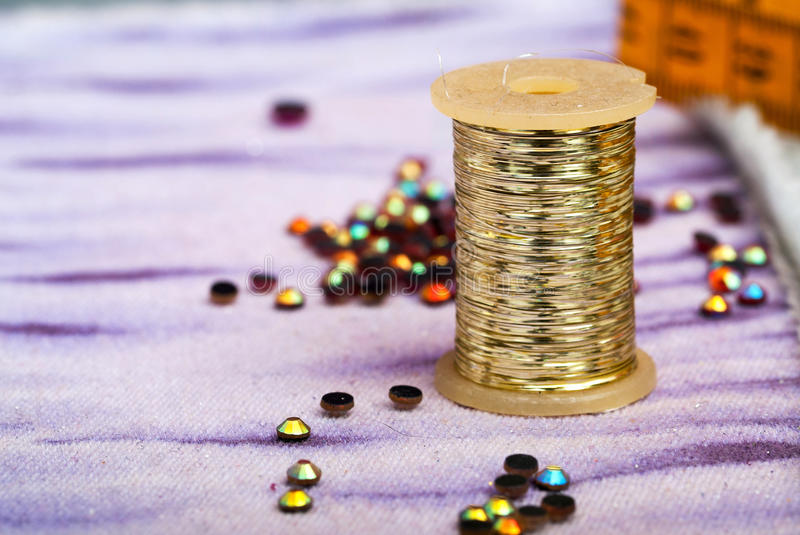 Sewing textile or cloth. Work table of a tailor. Measuring tape, reel of thread, and natural fabric. . Shallow depth of field. royalty free stock photo