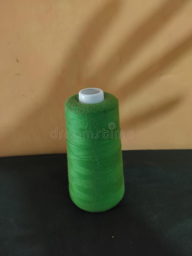 Sewing thread with a hand shadow background. Textile, craft, fashion, fabric, clothing, material, tailor, cotton, design, needlework, white, hobby, closeup stock photo