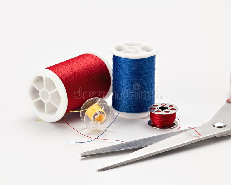 Sewing thread and a pair of scissors of different colors stock image
