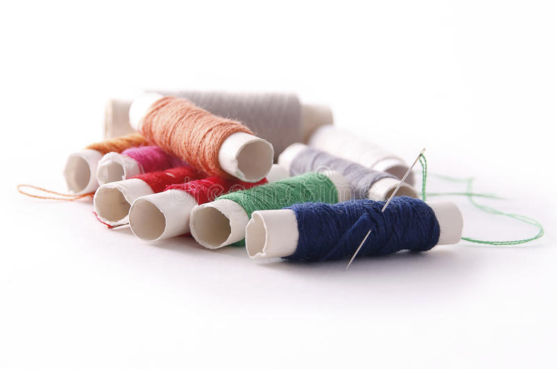 Sewing threads. Of different colors and a needle royalty free stock photography