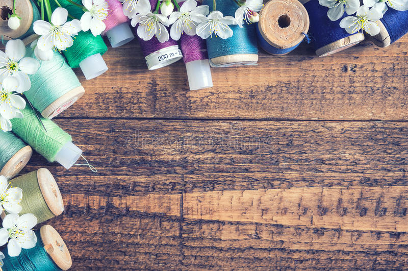 Sewing threads with cherry blossoms. On rustic wooden background stock image