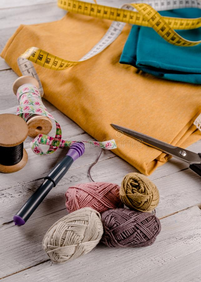 Sewing tool with colorful cloth on a wooden board stock photo