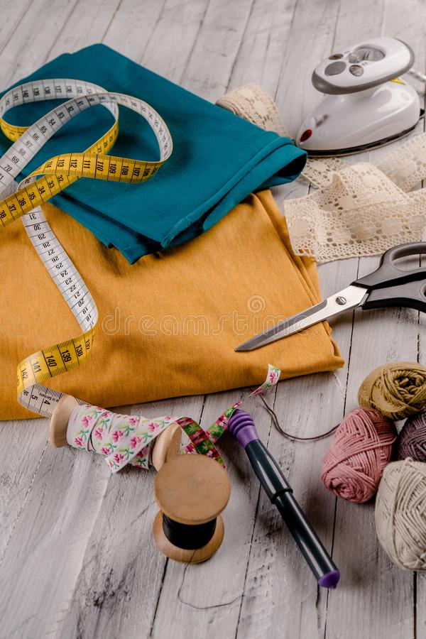 Sewing tool with colorful cloth on a wooden board royalty free stock photography
