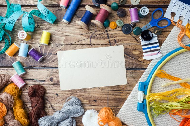 Sewing tool for needlework, colored threads centimeter and buttons with a pair of scissors on the table. Copy space stock photography
