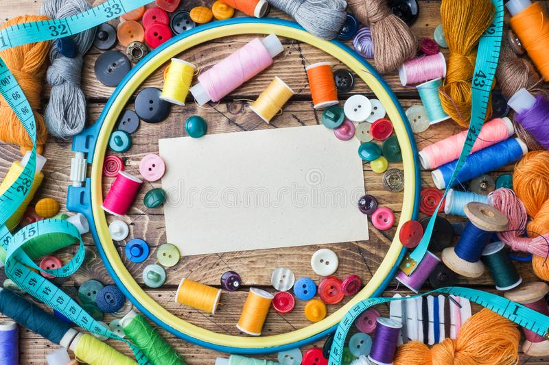 Sewing tool for needlework, colored threads centimeter and buttons with a pair of scissors on the table. Copy space royalty free stock image