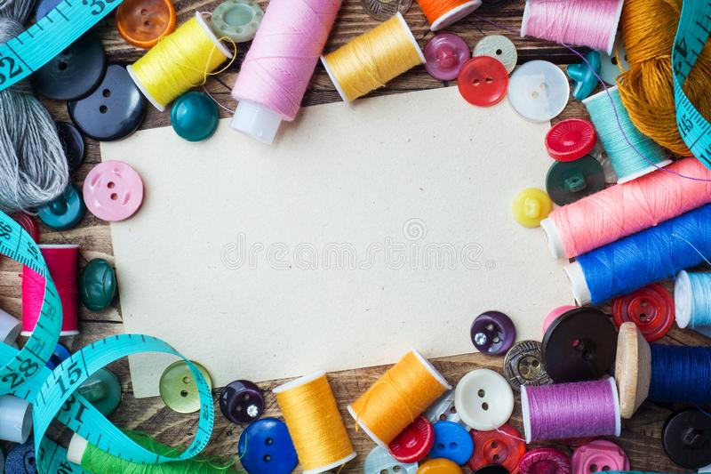 Sewing tool for needlework, colored threads centimeter and buttons with a pair of scissors on the table. Copy space. Sewing tool for needlework, colored threads royalty free stock photo