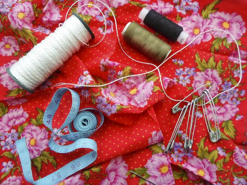 Sewing tools: colored sewing threads, centimeter ribbons and colored pins on a red background close-upвц stock photo