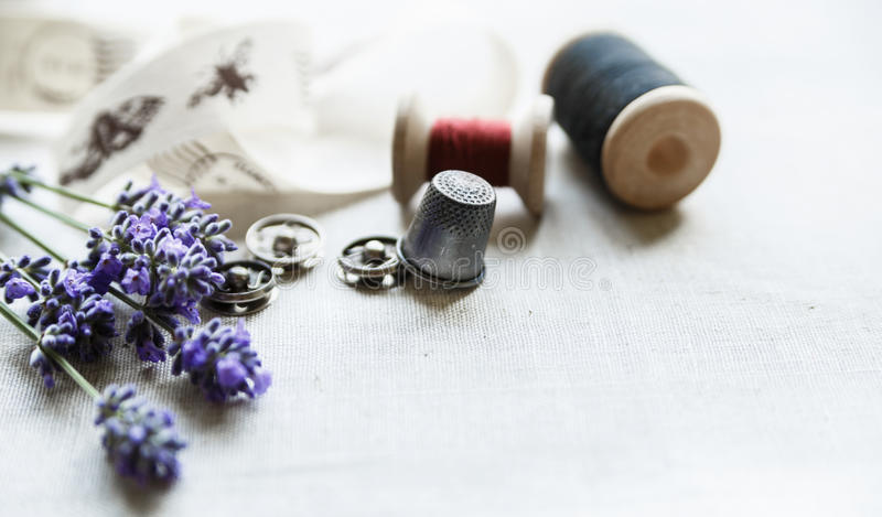 Sewing tools with fresh lavander flowers on linen background. Vintage wooden spool, braid, thimble, buttons. stock image