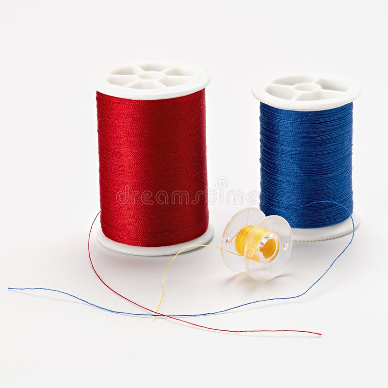 Red, blue and yellow colors of thread on spools ready for some s stock photography