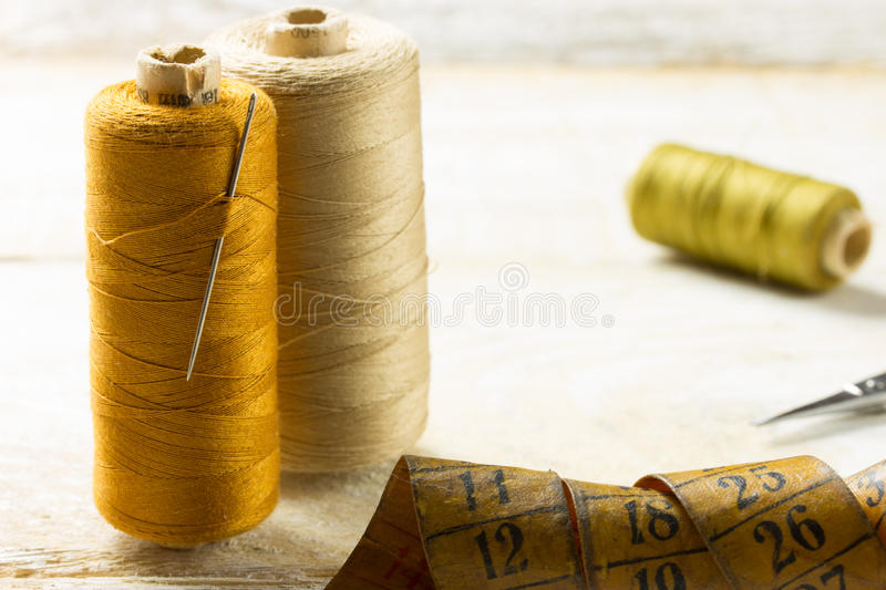 Sewing tools. An old style image of cotton reels and other sewing items on a wooden table stock photography