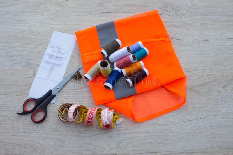 Sewing tools and sewing kit on wooden textured background. Thread, needles and cloth royalty free stock photo