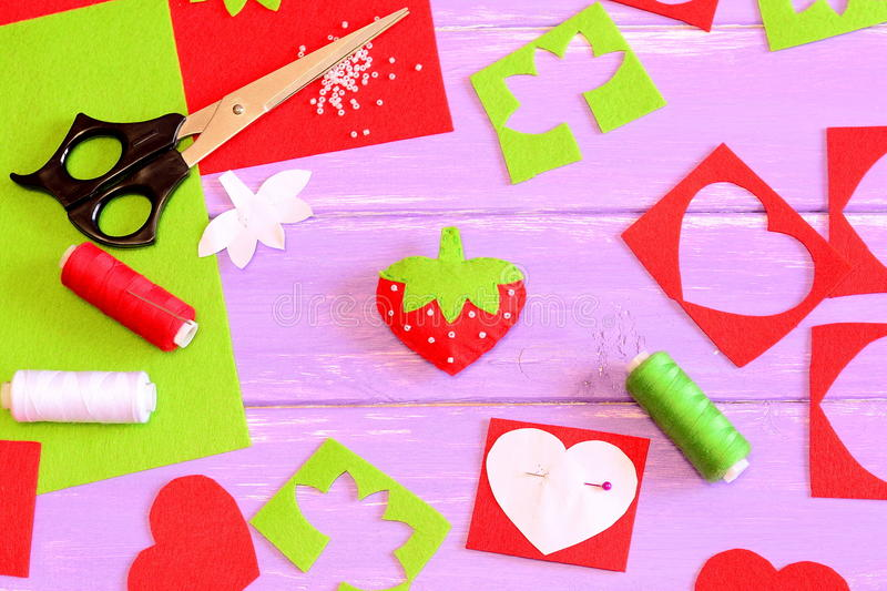 Sewing toy, tools and materials. Felt strawberry toy, scissors, red and green felt sheets and scraps, thread, needle, paper patter royalty free stock photos