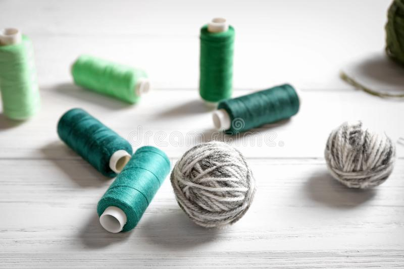 Sewing and woolen threads. On wooden background royalty free stock images