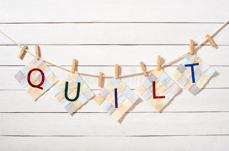 Sewn letters, combined as the word quilt, attached with clothespins on a rope. On a white wooden background stock images