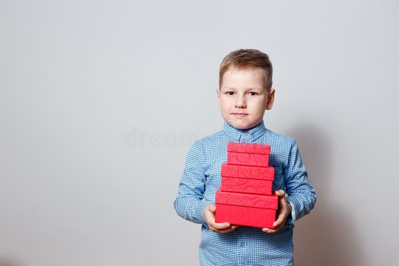 Sex-år-gammal pojke i en blå skjortainnehavgåva arkivfoto
