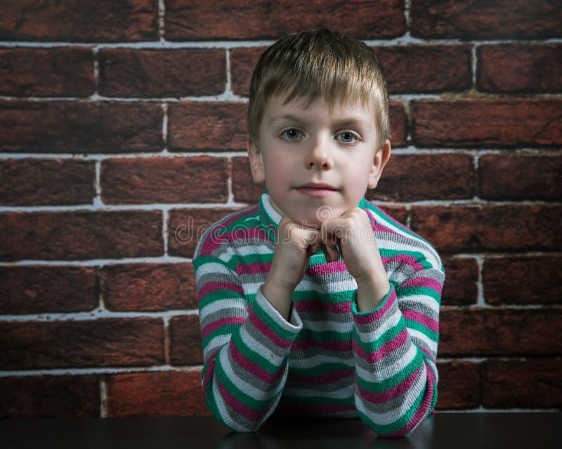 Sex-år-gammal pojke med ett ondsint uttryck royaltyfri foto