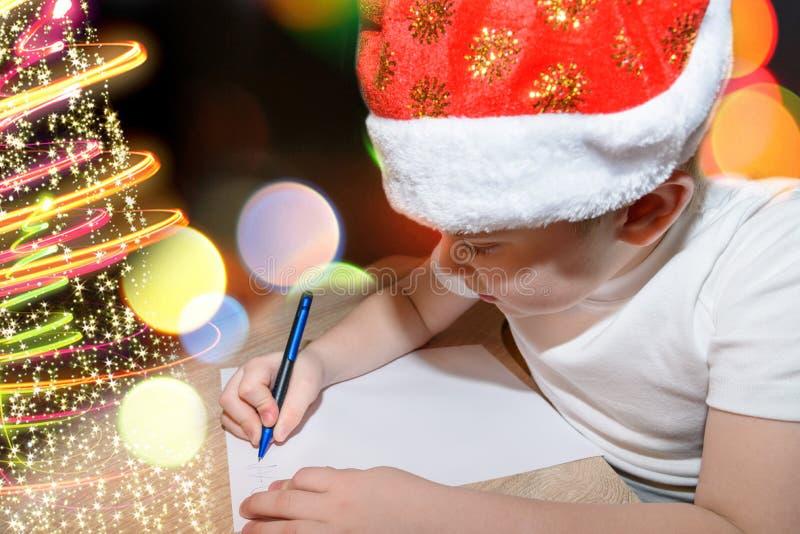 Sex åriga gulliga pojke med röd jul cap att skriva ett brev till Santa Claus nära julgranen inomhus Ljusa lodisar för nytt år royaltyfri fotografi