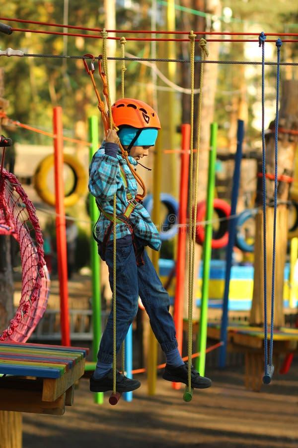 Sex åriga pojke som övervinner hinderkurs i repet, parkerar royaltyfria foton