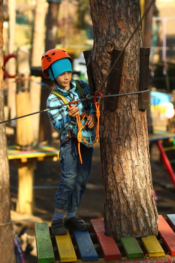 Sex åriga pojke som övervinner hinderkurs i repet, parkerar royaltyfri foto