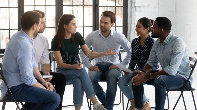Sex anställda sitter i stolar och diskuterar deltagande i seminarier royaltyfri fotografi