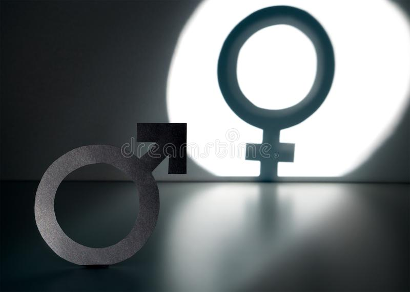 Sex change, gender reassignment, transgender and sexual identity. Concept. Male and man symbol in spotlight forming a female and woman sign in shadow on wall royalty free stock photos
