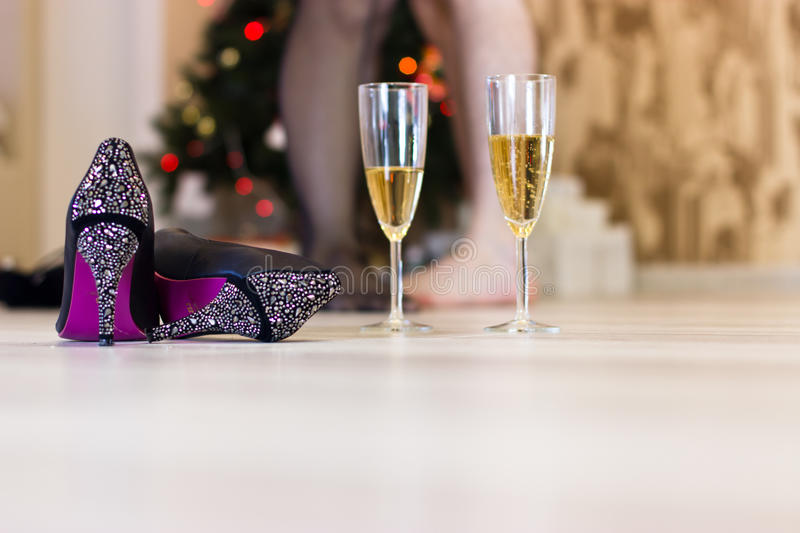 Sex after a Christmas party, quick sex concept. Shoes and sparkling wine in the foreground. Christmas tree and lovers in the background royalty free stock photos