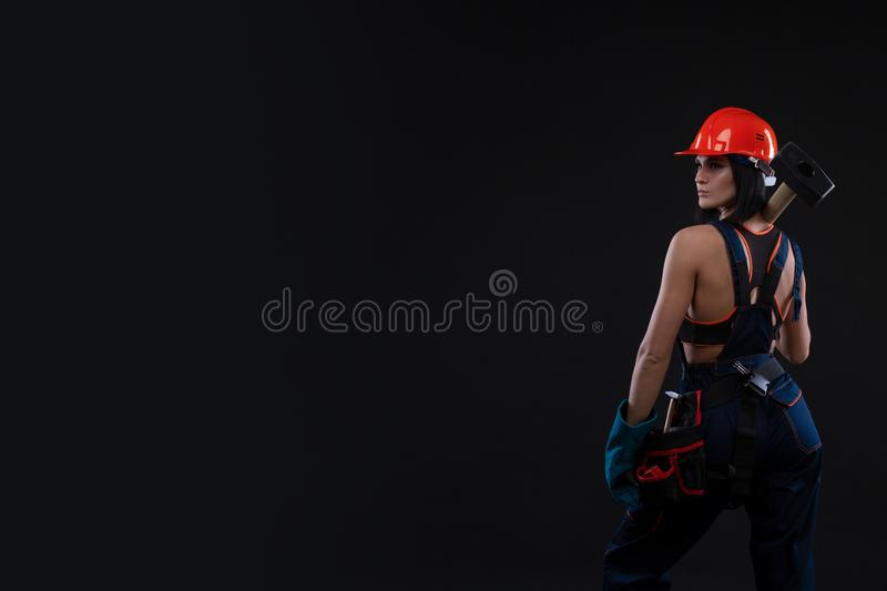 Sex equality and feminism. Back of girl holding hammer. Woman working as mechanic. stock image
