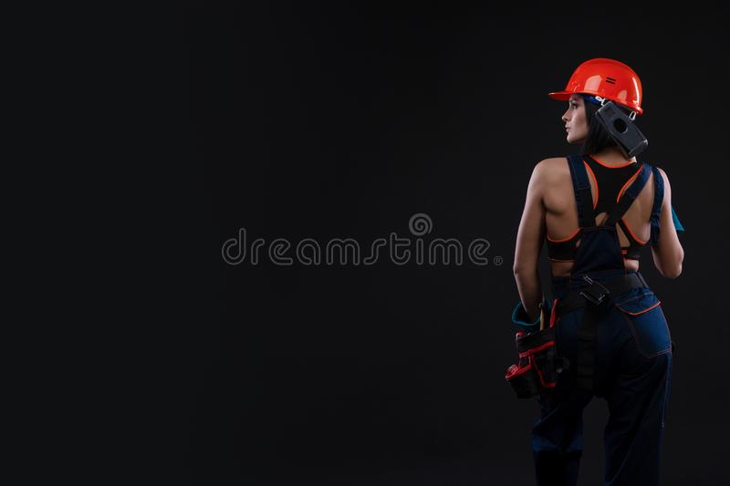 Sex equality and feminism. Back of girl holding hammer. Woman working as mechanic. royalty free stock images