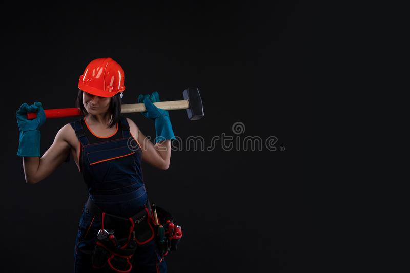 Sex equality and feminism. girl in safety helmet holding hammer tool. Attractive woman working as construction worker. stock photography