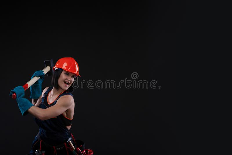Sex equality and feminism. girl in safety helmet holding hammer tool. Attractive woman working as construction worker. royalty free stock image