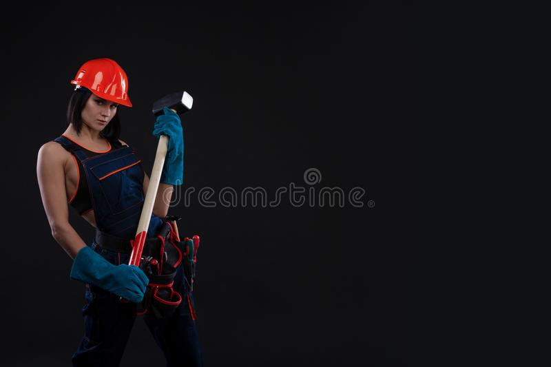 Sex equality and feminism. girl in safety helmet holding hammer tool. Attractive woman working as construction worker. stock images