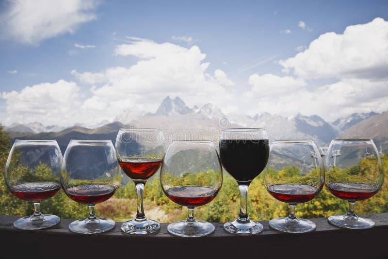 Sex exponeringsglas av konjak och ett exponeringsglas av rött vinställningen mot bakgrunden av en härlig berglandskap- och kabelb arkivfoto