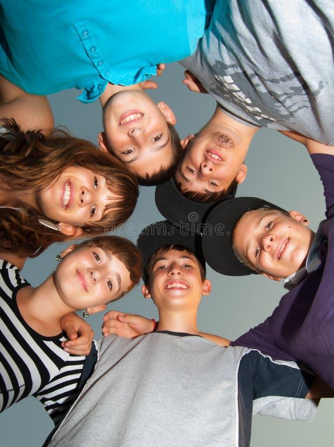Sex lyckliga tonåringar som plattforer i cirkeln royaltyfria foton
