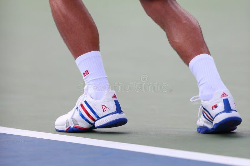 Sex mästare Novak Djokovic för storslagen Slam för tider bär beställnings- Adidas tennisskor under match på US Open 2014 royaltyfri bild