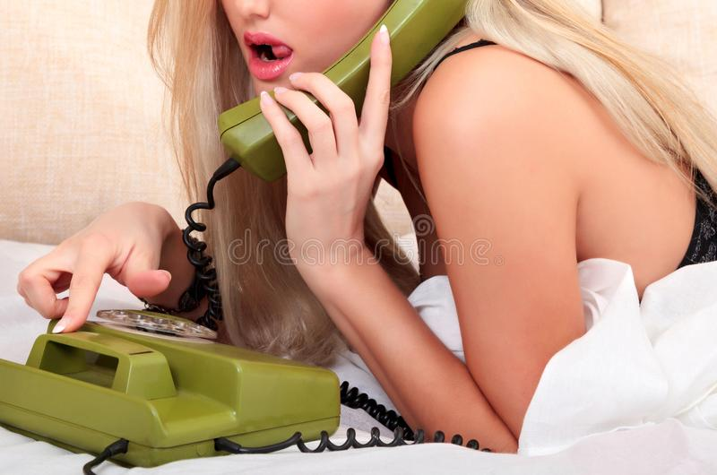 Sex on the phone. Woman laying in a bed stock image