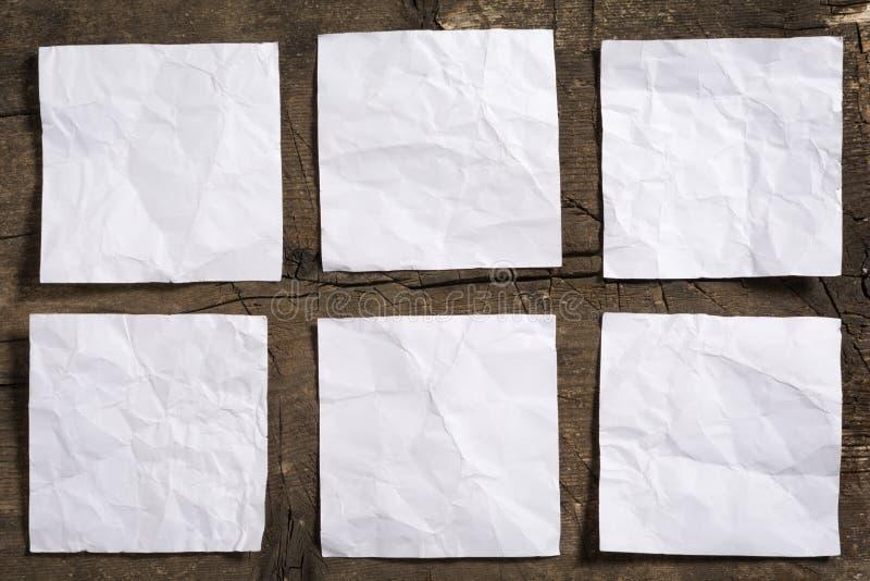 Sex skrynkliga tomma vita anmärkningslegitimationshandlingar på träyttersida royaltyfria foton